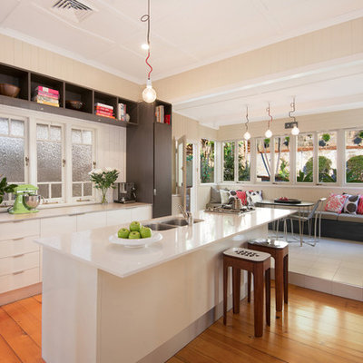 Inspiration for a contemporary galley medium tone wood floor eat-in kitchen remodel in Brisbane with a double-bowl sink, flat-panel cabinets, white cabinets, stainless steel appliances and an island