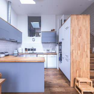 Photo of a medium sized contemporary u-shaped kitchen/diner in Hampshire with flat-panel cabinets, purple cabinets, wood worktops, white splashback, metro tiled splashback, white appliances, medium hardwood flooring, no island and brown floors.