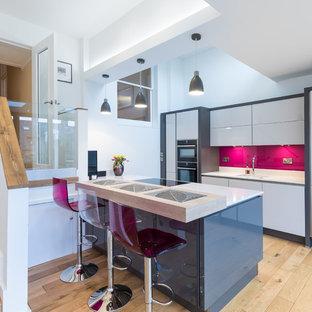 На фото: кухни в современном стиле с врезной раковиной, плоскими фасадами, белыми фасадами, розовым фартуком, черной техникой, светлым паркетным полом, островом и бежевым полом