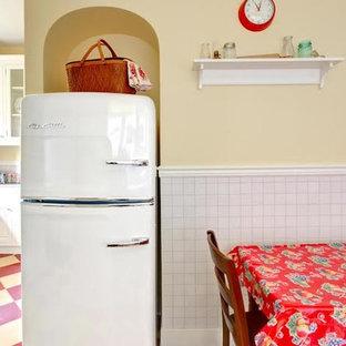 アトランタの中サイズのカントリー風おしゃれなキッチン (ドロップインシンク、レイズドパネル扉のキャビネット、白いキャビネット、人工大理石カウンター、白いキッチンパネル、ガラスタイルのキッチンパネル、白い調理設備、クッションフロア、アイランドなし、赤い床) の写真