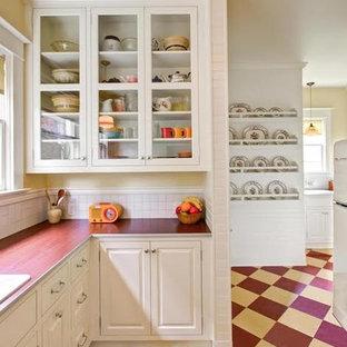 アトランタの中くらいのカントリー風おしゃれなキッチン (ドロップインシンク、レイズドパネル扉のキャビネット、白いキャビネット、人工大理石カウンター、白いキッチンパネル、ガラスタイルのキッチンパネル、白い調理設備、クッションフロア、アイランドなし、赤い床) の写真
