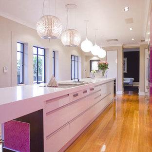 Inspiration för stora moderna parallellkök, med en undermonterad diskho, släta luckor, vita skåp, bänkskiva i kvarts, rosa stänkskydd, glaspanel som stänkskydd, rostfria vitvaror, ljust trägolv och en köksö