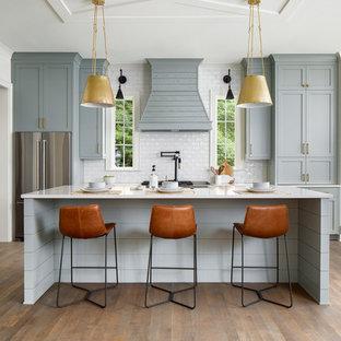 シャーロットのカントリー風おしゃれなキッチン (シェーカースタイル扉のキャビネット、白いキッチンパネル、サブウェイタイルのキッチンパネル、シルバーの調理設備、無垢フローリング、茶色い床、白いキッチンカウンター、グレーのキャビネット) の写真