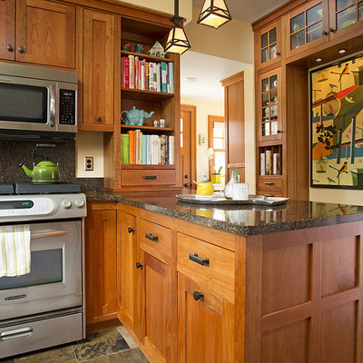 Example of a large arts and crafts u-shaped slate floor eat-in kitchen design in Minneapolis with an undermount sink, shaker cabinets, medium tone wood cabinets, quartz countertops, stainless steel appliances and a peninsula