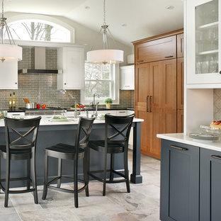 Transitional kitchen ideas - Inspiration for a transitional l-shaped kitchen remodel in New York with shaker cabinets, blue cabinets, brown backsplash, subway tile backsplash and paneled appliances