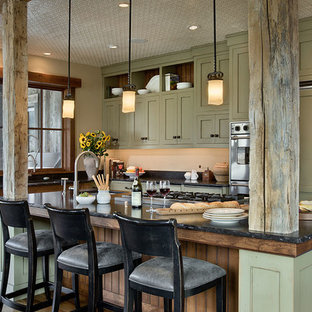 Inspiration for a rustic l-shaped kitchen/diner in Other with a submerged sink, green cabinets, granite worktops, an island, black splashback, stone slab splashback, stainless steel appliances, plywood flooring, brown floors and black worktops.