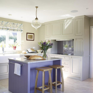 Photo of a medium sized classic l-shaped kitchen in Other with a belfast sink, recessed-panel cabinets, grey cabinets, glass sheet splashback, an island, grey floors and grey worktops.