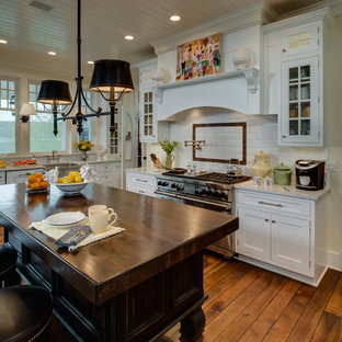 Example of a classic kitchen design in Detroit with recessed-panel cabinets, white cabinets, white backsplash, subway tile backsplash and stainless steel appliances