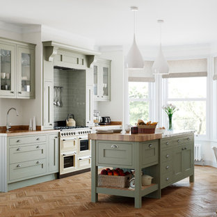 This is an example of a traditional single-wall kitchen/diner in Manchester with a submerged sink, shaker cabinets, green cabinets, wood worktops, green splashback, integrated appliances, medium hardwood flooring, an island, brown floors and brown worktops.