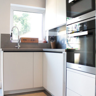This is an example of a small modern l-shaped kitchen/diner in London with a built-in sink, flat-panel cabinets, white cabinets, granite worktops, grey splashback, porcelain splashback, black appliances, porcelain flooring and an island.