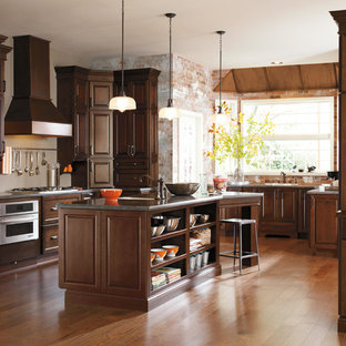 Inspiration for a large traditional u-shaped eat-in kitchen in Other with an undermount sink, raised-panel cabinets, dark wood cabinets, quartz benchtops, brown splashback, brick splashback, stainless steel appliances, medium hardwood floors, with island, multi-coloured floor and multi-coloured benchtop.