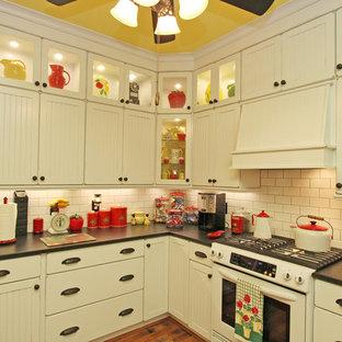 アトランタの中サイズのおしゃれなキッチン (エプロンフロントシンク、シェーカースタイル扉のキャビネット、御影石カウンター、白いキッチンパネル、サブウェイタイルのキッチンパネル、白い調理設備、無垢フローリング、マルチカラーの床、黒いキッチンカウンター) の写真