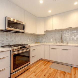Kleine Moderne Wohnküche in U-Form mit Unterbauwaschbecken, flächenbündigen Schrankfronten, weißen Schränken, Quarzwerkstein-Arbeitsplatte, Küchenrückwand in Weiß, Rückwand aus Glasfliesen, Küchengeräten aus Edelstahl, hellem Holzboden, Kücheninsel, orangem Boden und weißer Arbeitsplatte in Sonstige