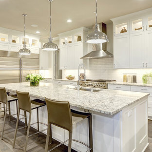 Large transitional eat-in kitchen ideas - Eat-in kitchen - large transitional l-shaped light wood floor eat-in kitchen idea in New York with an undermount sink, shaker cabinets, white cabinets, white backsplash, subway tile backsplash, stainless steel appliances, an island and granite countertops