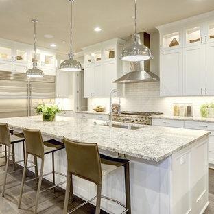 Große Klassische Wohnküche in L-Form mit Unterbauwaschbecken, Schrankfronten im Shaker-Stil, weißen Schränken, Küchenrückwand in Weiß, Rückwand aus Metrofliesen, Küchengeräten aus Edelstahl, hellem Holzboden, Kücheninsel und Granit-Arbeitsplatte in New York