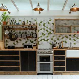Inspiration for a scandi single-wall enclosed kitchen in London with a belfast sink, flat-panel cabinets, black cabinets, wood worktops, multi-coloured splashback, coloured appliances, painted wood flooring, no island and ceramic splashback.
