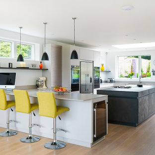 Photo of a large contemporary u-shaped kitchen in Gloucestershire with flat-panel cabinets, composite countertops, an island, grey worktops, grey cabinets, stainless steel appliances, medium hardwood flooring and brown floors.