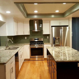 Large traditional l-shaped enclosed kitchen in San Francisco with a double-bowl sink, shaker cabinets, white cabinets, granite worktops, green splashback, glass tiled splashback, stainless steel appliances, light hardwood flooring, an island, brown floors and multicoloured worktops.