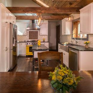 シカゴの中くらいのインダストリアルスタイルのおしゃれなキッチン (エプロンフロントシンク、シェーカースタイル扉のキャビネット、白いキャビネット、ソープストーンカウンター、白いキッチンパネル、磁器タイルのキッチンパネル、シルバーの調理設備、濃色無垢フローリング) の写真