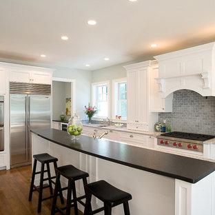 Новый формат декора квартиры: кухня в классическом стиле с техникой из нержавеющей стали, столешницей из кварцевого композита, фасадами с утопленной филенкой, белыми фасадами, синим фартуком и фартуком из сланца