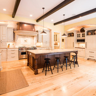 Inspiration for a large mediterranean u-shaped kitchen in DC Metro with a farmhouse sink, raised-panel cabinets, beige cabinets, granite benchtops, beige splashback, panelled appliances, light hardwood floors, with island, beige floor and multi-coloured benchtop.