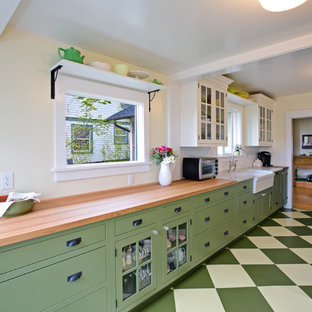 Example of an arts and crafts u-shaped painted wood floor enclosed kitchen design in Seattle with a farmhouse sink, glass-front cabinets, green cabinets, wood countertops, white backsplash, subway tile backsplash, stainless steel appliances and an island