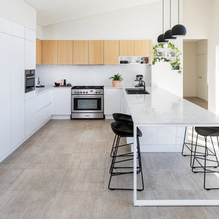 This is an example of a contemporary u-shaped kitchen in Perth with a drop-in sink, flat-panel cabinets, white cabinets, white splashback, panelled appliances, a peninsula, beige floor and grey benchtop.