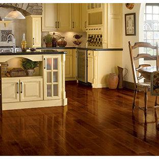 Exempel på ett avskilt, stort lantligt svart svart u-kök, med en undermonterad diskho, luckor med upphöjd panel, gula skåp, granitbänkskiva, rostfria vitvaror, mörkt trägolv, en köksö och brunt golv