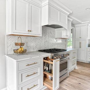 ニューヨークの広いトランジショナルスタイルのおしゃれなキッチン (アンダーカウンターシンク、インセット扉のキャビネット、白いキャビネット、クオーツストーンカウンター、白いキッチンパネル、モザイクタイルのキッチンパネル、パネルと同色の調理設備、白いキッチンカウンター) の写真