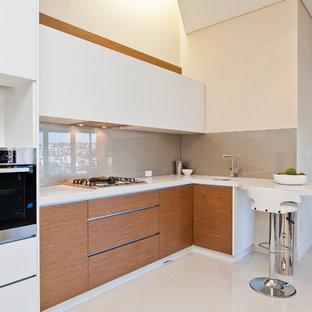 パースの小さいコンテンポラリースタイルのおしゃれなキッチン (アンダーカウンターシンク、フラットパネル扉のキャビネット、白いキャビネット、ベージュキッチンパネル、ガラス板のキッチンパネル、クオーツストーンカウンター、シルバーの調理設備の、磁器タイルの床) の写真