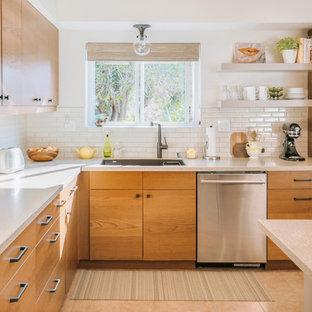 Inspiration för ett 50 tals beige beige l-kök, med en undermonterad diskho, släta luckor, skåp i mellenmörkt trä, vitt stänkskydd, stänkskydd i tunnelbanekakel, rostfria vitvaror, en köksö och beiget golv