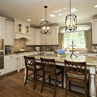 ローリーのトラディショナルスタイルのおしゃれなL型キッチン (白いキャビネット、茶色いキッチンパネル、シルバーの調理設備、石タイルのキッチンパネル) の写真