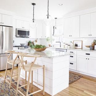 ブリッジポートの小さいカントリー風おしゃれなキッチン (エプロンフロントシンク、シェーカースタイル扉のキャビネット、白いキャビネット、クオーツストーンカウンター、白いキッチンパネル、サブウェイタイルのキッチンパネル、シルバーの調理設備の、茶色い床、グレーのキッチンカウンター、無垢フローリング) の写真