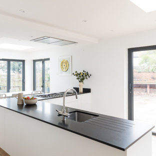 Design ideas for a large scandi l-shaped kitchen/diner in London with a submerged sink, flat-panel cabinets, white cabinets, quartz worktops, light hardwood flooring, a breakfast bar, black worktops and beige floors.