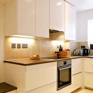ロンドンの中くらいのモダンスタイルのおしゃれなキッチン (シングルシンク、ラミネートカウンター、ベージュキッチンパネル、セラミックタイルのキッチンパネル、白い調理設備、セラミックタイルの床、アイランドなし、ベージュの床、茶色いキッチンカウンター) の写真