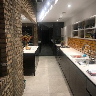 ロンドンの中くらいのコンテンポラリースタイルのおしゃれなキッチン (ドロップインシンク、フラットパネル扉のキャビネット、黒いキャビネット、大理石カウンター、茶色いキッチンパネル、レンガのキッチンパネル、黒い調理設備、セメントタイルの床、ベージュの床、白いキッチンカウンター) の写真