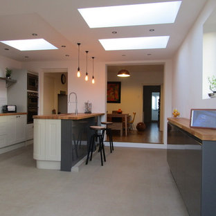 Expansive contemporary u-shaped eat-in kitchen in Devon with an undermount sink, louvered cabinets, beige cabinets, wood benchtops, white splashback, ceramic splashback, stainless steel appliances, vinyl floors and a peninsula.