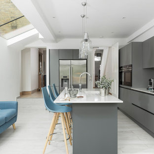 Design ideas for a contemporary l-shaped kitchen in Surrey with a submerged sink, flat-panel cabinets, grey cabinets, white splashback, stainless steel appliances, an island, grey floors and white worktops.