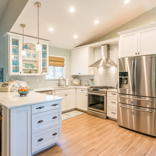 Design ideas for a mid-sized beach style u-shaped eat-in kitchen in Sacramento with an undermount sink, glass-front cabinets, white cabinets, marble benchtops, white splashback, glass tile splashback, stainless steel appliances, ceramic floors and a peninsula.
