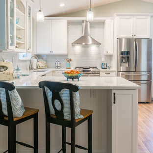 Photo of a mid-sized beach style u-shaped eat-in kitchen in Sacramento with an undermount sink, glass-front cabinets, white cabinets, marble benchtops, white splashback, glass tile splashback, stainless steel appliances, ceramic floors and a peninsula.
