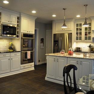 Exempel på ett mellanstort klassiskt l-kök, med en undermonterad diskho, luckor med upphöjd panel, vita skåp, granitbänkskiva, vitt stänkskydd, stänkskydd i stenkakel, rostfria vitvaror, skiffergolv, en köksö och svart golv