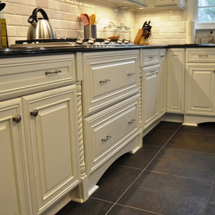 Mid-sized traditional kitchen inspiration - Inspiration for a mid-sized timeless l-shaped slate floor and black floor kitchen remodel in DC Metro with an undermount sink, raised-panel cabinets, white cabinets, granite countertops, white backsplash, stone tile backsplash, stainless steel appliances and an island