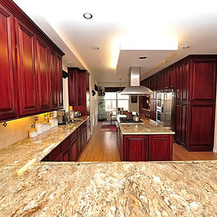 Large u-shaped kitchen pantry in Denver with a double-bowl sink, raised-panel cabinets, medium wood cabinets, granite worktops, beige splashback, stone tiled splashback, stainless steel appliances, light hardwood flooring and an island.