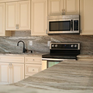 Mid-sized transitional kitchen ideas - Mid-sized transitional l-shaped kitchen photo in DC Metro with an undermount sink, raised-panel cabinets, white cabinets, granite countertops, gray backsplash, stainless steel appliances and an island