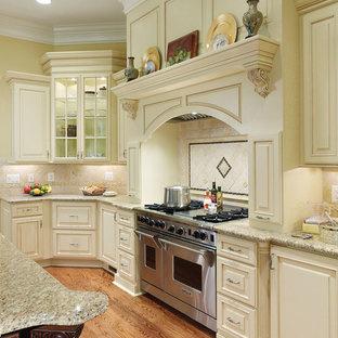 Diseño de cocina en U, tradicional, grande, con armarios con paneles con relieve, puertas de armario blancas, encimera de granito, salpicadero beige, salpicadero de azulejos de piedra, electrodomésticos con paneles, suelo de madera en tonos medios, una isla y suelo marrón
