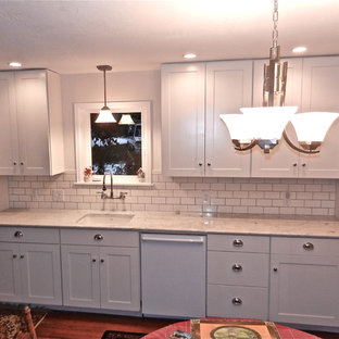 Example of an arts and crafts single-wall medium tone wood floor eat-in kitchen design in Seattle with an undermount sink, shaker cabinets, white cabinets, marble countertops, white backsplash, subway tile backsplash and white appliances