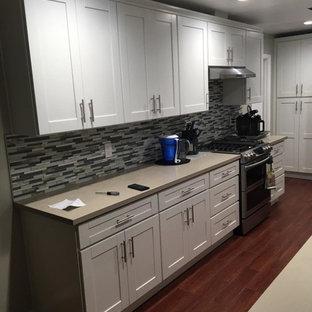 ロサンゼルスの小さいトランジショナルスタイルのおしゃれなキッチン (アンダーカウンターシンク、シェーカースタイル扉のキャビネット、白いキャビネット、人工大理石カウンター、グレーのキッチンパネル、ボーダータイルのキッチンパネル、シルバーの調理設備、無垢フローリング、アイランドなし、青い床、グレーのキッチンカウンター) の写真