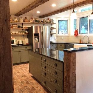 サンルイスオビスポの中くらいのカントリー風おしゃれなキッチン (エプロンフロントシンク、レイズドパネル扉のキャビネット、緑のキャビネット、クオーツストーンカウンター、白いキッチンパネル、ガラスタイルのキッチンパネル、シルバーの調理設備、磁器タイルの床、赤い床) の写真