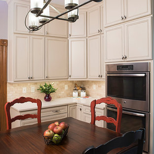 Small traditional eat-in kitchen designs - Example of a small classic l-shaped medium tone wood floor and brown floor eat-in kitchen design in St Louis with a double-bowl sink, white cabinets, solid surface countertops, multicolored backsplash, subway tile backsplash, stainless steel appliances and no island