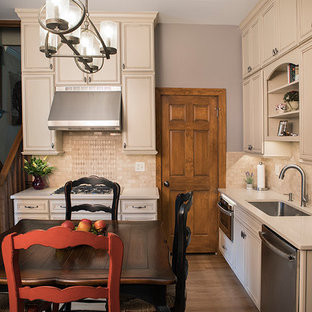 Small traditional eat-in kitchen appliance - Eat-in kitchen - small traditional l-shaped medium tone wood floor and brown floor eat-in kitchen idea in St Louis with a double-bowl sink, white cabinets, solid surface countertops, multicolored backsplash, subway tile backsplash, stainless steel appliances and no island